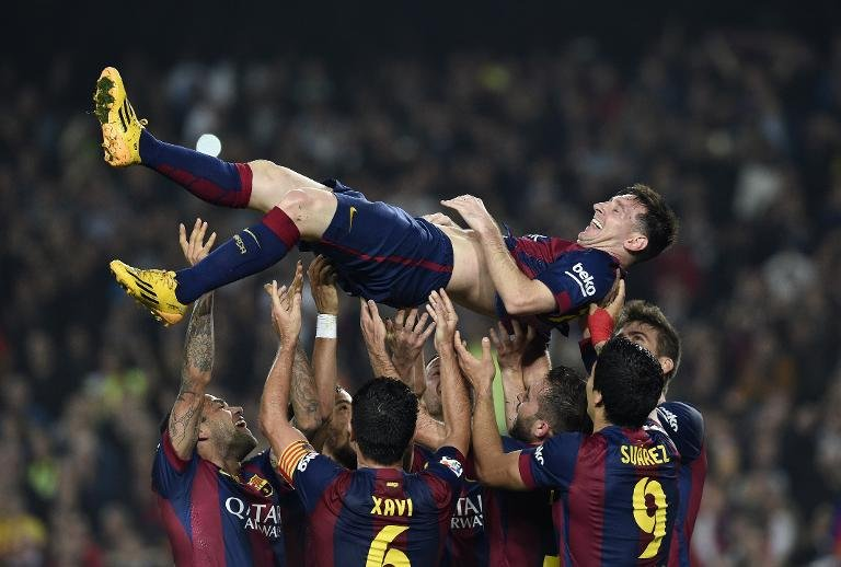 Barcelona's Argentinian forward Lionel Messi (top) is thrown into the air by his teammates as they celebrate his new record after he scored during the Spanish league football match FC Barcelona vs Sevilla FC in Barcelona on November 22, 2014