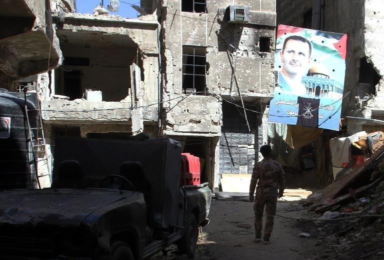 A man walks under a portrait of Syrian President Bashar al-Assad on a street inside the Yarmuk Palestinian refugee camp in Damascus on April 6, 2015