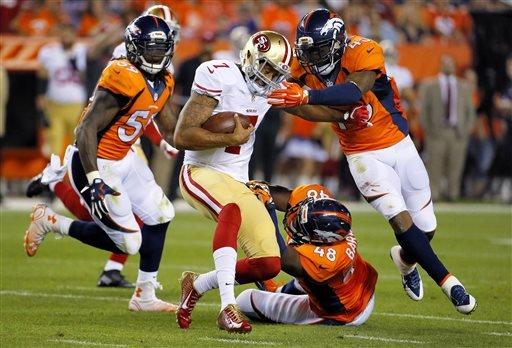 San Francisco 49ers quarterback Colin Kaepernick (7) is tackled by Denver Broncos' Shaquil Barrett (48), T.J. Ward (43) and Danny Trevathan (59) during the first half of an NFL preseason football game, Saturday, Aug. 29, 2015, in Denver. (AP Photo/Jack Dempsey)