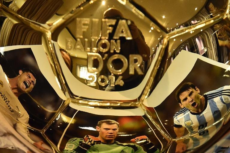 (From L) Images of Cristiano Ronaldo, Manuel Neuer and Lionel Messi are reflected in the Ballon d'Or trophy displayed at Mellerio jewellery house in Paris, on December 15, 2014