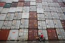 A woman rides her motorcycle past shipping containers at the Port of Shanghai