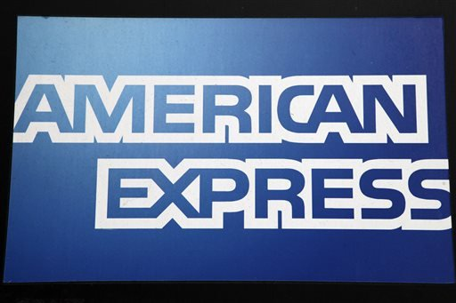 FILE - This Jan. 21, 2015 file photo shows a sign for American Express outside a New York business. American Express on Wednesday, Oct. 21, 2015 reported a 16 percent drop in profits from a year earlier, missing analysts estimates, as the credit card company was hurt by higher expenses and remains under pressure from the strong U.S. dollar. The company also cut its full-year forecast. (AP Photo/Mark Lennihan, File)