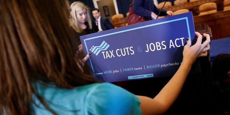 A congressional aide places a placard on a podium for the House Republican's legislation to overhaul the tax code on Capitol Hill in Washington, U.S., November 2, 2017.   REUTERS/Joshua Roberts