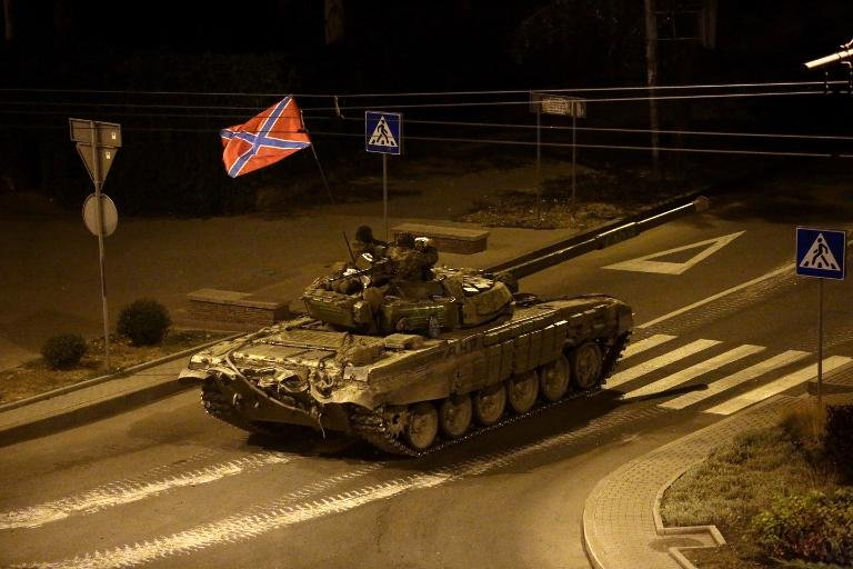A tank with a flag of Novorossia (union of Donetsk people's republic and Lugansk people's republic) drives in central Donetsk late on August 23, 2014