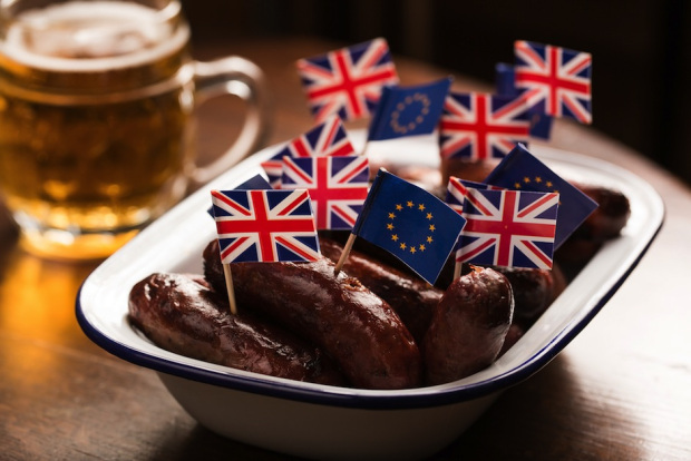 British Union Flags, commonly known as Union Jacks, and European Union (EU) flags stand on cocktail sticks in a dish of sausages on a table.