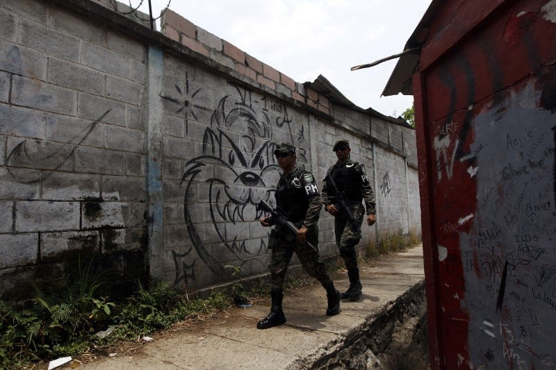 Military policemen walk past the graffiti of a street gang as they patrol the perimeter of the Saul Zelaya Institute, which is under military protection after a series of threats by gangs trying to control territory and drug sale points, in Tegucigalpa, Honduras, April 27, 2016. REUTERS/Jorge Cabrera