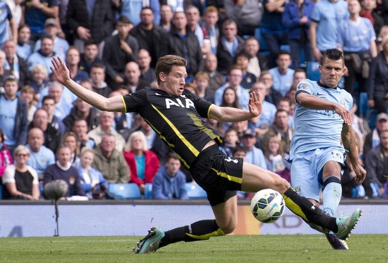 Manchester City's Argentinian striker Sergio Aguero (right) scores his, and their fourth goal past Tottenham Hotspur's Belgian defender Jan Vertonghen during the English Premier League match at the The Etihad Stadium in Manchester on October 18, 2014