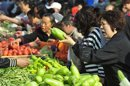 A customer bargains with a vendor for eggplants at an open-air food market in Shenyang