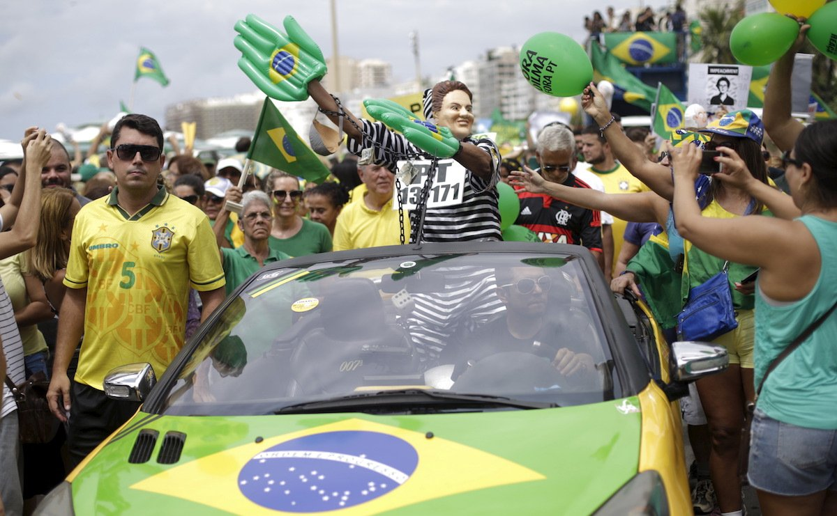 A demonstrator wearing a mask depicting Brazil's President Dilma Rousseff waves to people as they attend a protest against Rousseff, part of nationwide protests calling for her impeachment, at Copacabana beach in Rio de Janeiro, Brazil, March 13, 2016.