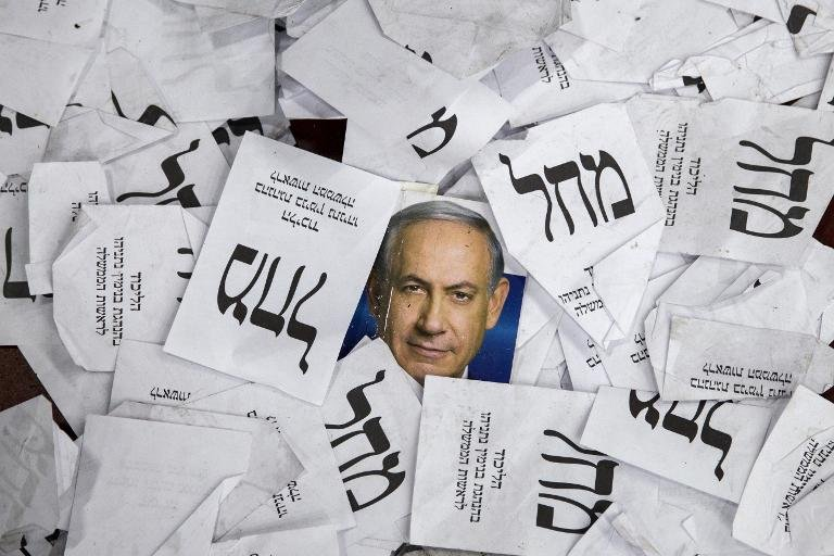 Copies of ballot papers and campaign posters for Israel's Prime Minister Benjamin Netanyahu's Likud Party lie on the ground in the aftermath of the country's parliamentary elections, early on March 18, 2015 in Tel Aviv
