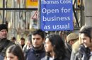 Pedestrian walk near a sign outside a branch of Thomas Cook in London