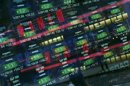 Stock prices on monitors are seen through a window to the street at the NASDAQ Market Site in New York