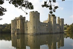 A castle of square plan surrounded by a water-filled moat. It has round corner towers and a forbidding appearance 1
