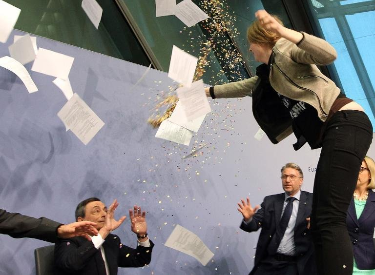 A woman disrupts a press conference by Mario Draghi (C), President of the European Central Bank, on April 15, 2015