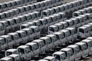 Newly produced trucks are seen at an industrial port before they are loaded to a cargo ship in Yokohama