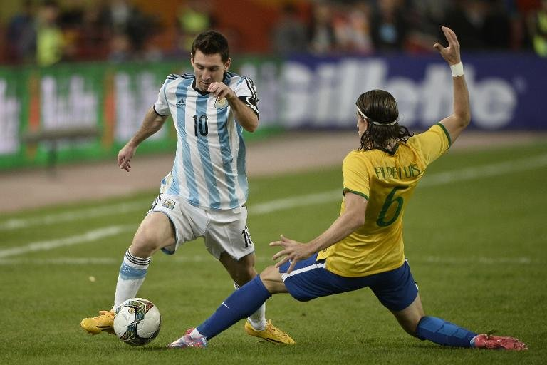 Brazil's Luis Felipe (right) challenges Argentina's Lionel Messi fights for the ball during the Superclasico at the National Stadium in Beijing on October 11, 2014