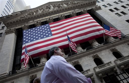 FILE - In this Monday, Aug. 8, 2011, file photo, a pedestrian walks past the New York Stock Exchange. World stock markets were mostly higher Monday, Aug. 17, 2015, as the yuan steadied and Greece inched closer to receiving its latest bailout. (AP Photo/Jin Lee, File)