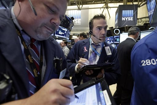Trader Gregory Rowe, center, works on the floor of the New York Stock Exchange, Monday, Nov. 2, 2015. Stocks opened slightly higher on Wall Street as the market comes off its biggest monthly gain in four years. Health care stocks were among the early winners. (AP Photo/Richard Drew)