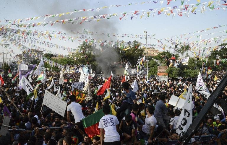 People look at smoke from an explosion during a rally by the pro-Kurdish People's Democratic Party on June 5, 2015 in Diyarbakir