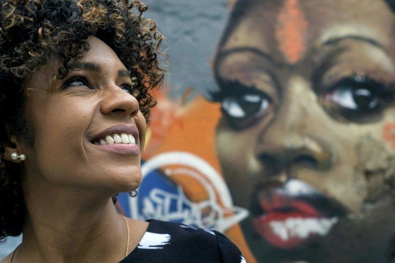 Brazilian journalist Luciana Barreto, 38, poses next to graffiti depicting a woman of African origin in Rio de Janeiro on July 9, 2015