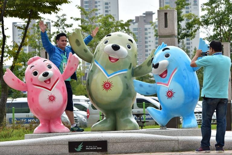 Journalists take pictures with Asian Games mascots outside the media center in Incheon on September 17, 2014