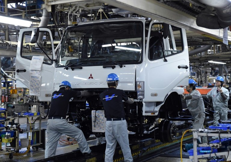 Workers assemble a truck at the Mitsubishi Fuso Truck and Bus Corporation (MFTBC) Kawasaki plant, in March 2015