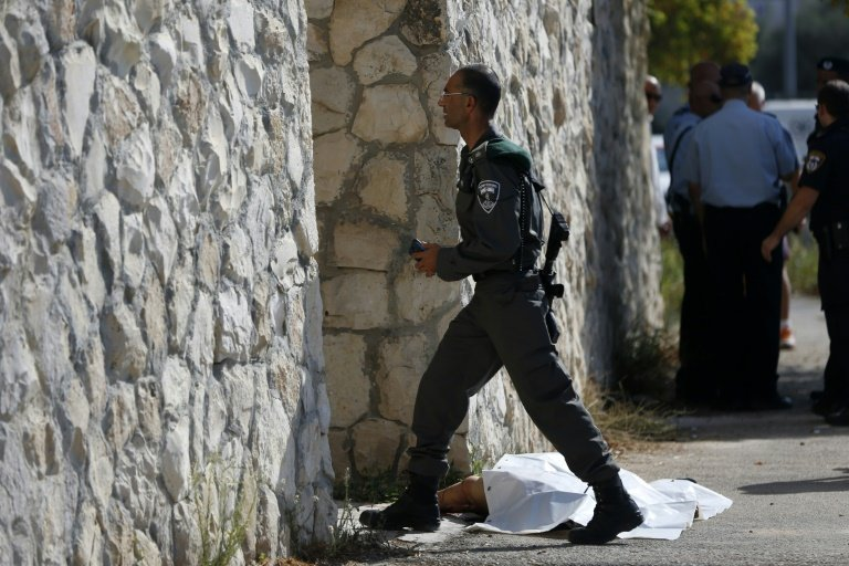 An Israeli border guard walks past the body of a Palestinian man who attempted to stab a soldier in the east Jerusalem Jewish settlement of Armon Hanatsiv, adjacent to the Palestinian neighbourhood of Jabal Mukaber, on October 17, 2015