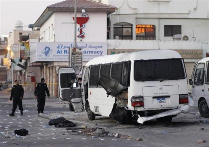 A police special unit arrives to inspect the police patrol mini bus which was hit by explosions at a police checkpoint in the village of Dih, west of Manama, February 14, 2014. REUTERS/Hamad I Mohammed