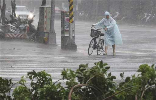 Behind fallen trees, a man braves the strong winds from Typhoon Soudelor with his bicycle in Taipei, Taiwan, Saturday, Aug. 8, 2015. Soudelor is bringing heavy rains and strong winds to the island Saturday with winds speeds over 170 kph (100 mph) and gusts over 200 kph (120 mph), according to Taiwan's Central Weather Bureau. (AP Photo/Wally Santana)