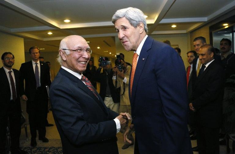 US Secretary of State John Kerry is greeted by Pakistan's National Security Advisor Sartaj Aziz (L) shortly after arriving in Islamabad on January 12, 2015