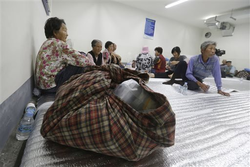 South Korean residents gather at a shelter in Yeoncheon, south of the demilitarized zone that divides the two Koreas, South Korea, Friday, Aug. 21, 2015. South Korea fired dozens of shells Thursday at rival North Korea after the North lobbed several rounds across the world's most heavily armed border and threatened to take further action unless Seoul ends its loudspeaker broadcasts. The North denied it fired any shots and warned of retaliation for what it called a serious provocation. (AP Photo/Ahn Young-joon)