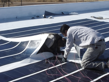 Workers installing solar panels on reservation building