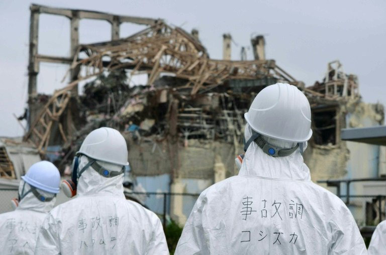 Members of a Japanese government panel inspect the damaged building housing reactor number three at the Fukushima Dai-ichi nuclear power plant on June 17, 2011