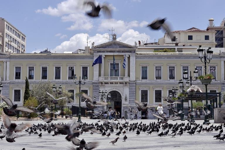 Pigeons fly in front of the National Bank of Greece headquarters in central Athens on June 23, 2015