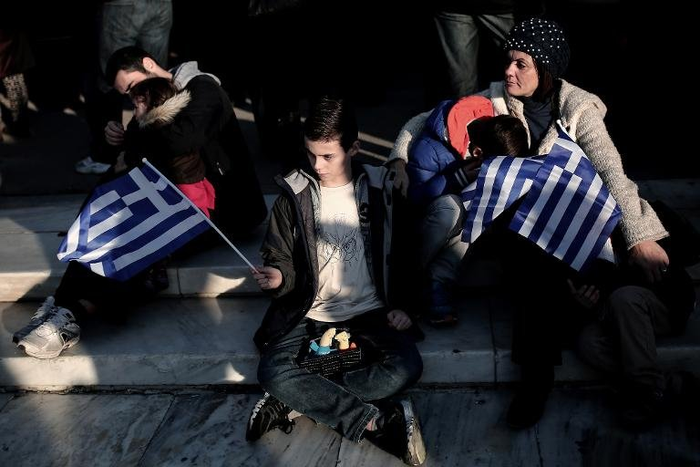A boy holds a Greek flag during an anti-austerity, pro-government demonstration in front of the Parliament in Athens, on February 15, 2015