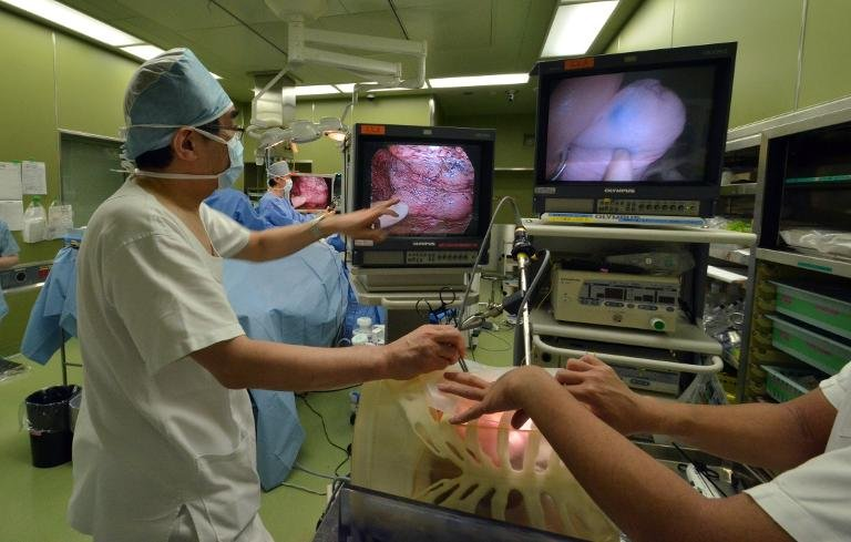 Professor Toshiaki Morikawa (L) gives a lesson while using a 3D-printed lung at the Jikei University hospital in Tokyo
