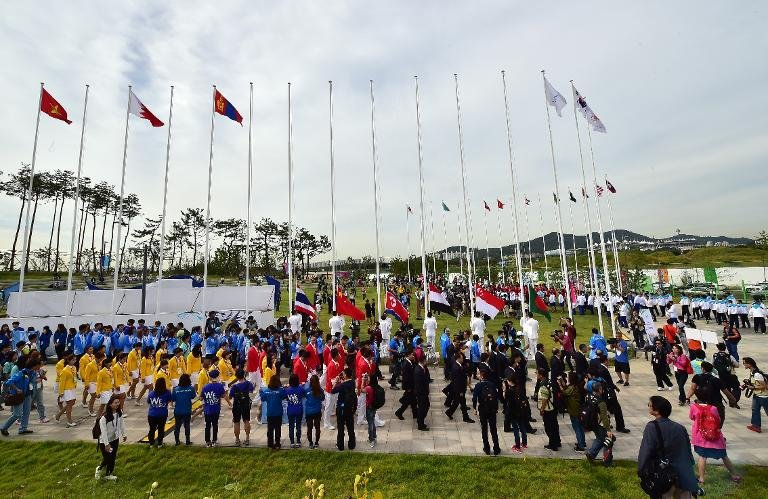 Chinese team members (yellow and red uniforms) attend a team welcoming ceremony at the athletes village of the Asian Games in Incheon on September 18, 2014