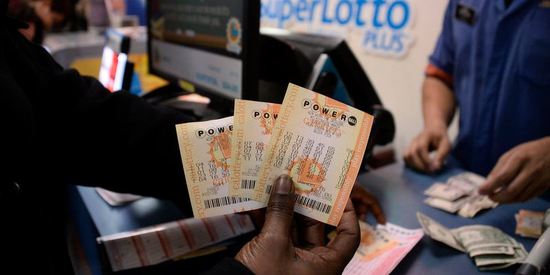 A customer shows their tickets for the Powerball lottery at the CA lotto store in San Bernardino County, California on the California-Nevada state line January 9, 2016.   REUTERS/Gene Blevins