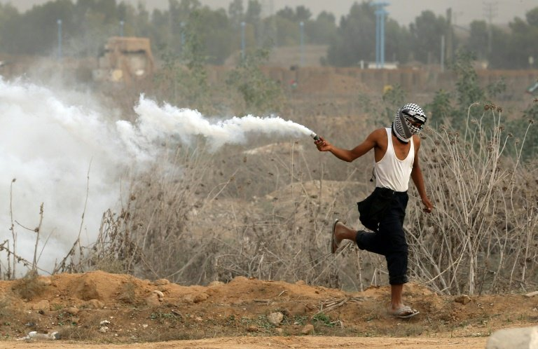 A Palestinian protester runs holding a tear gas canister during clashes with Israeli security forces near the border between Israeli and Gaza on October 23, 2015