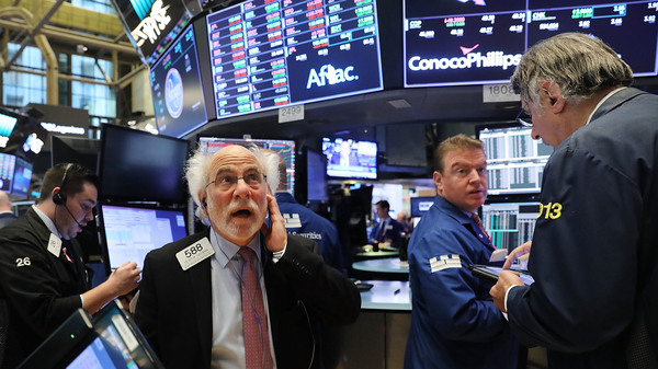 Traders work on the floor of the New York Stock Exchange on Oct. 11. The Dow Jones Industrial Average crossed 23,000 for the first time on Tuesday.